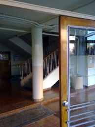 Tágas előtér jó anyagokkal igényesen burkolva. Bár a szőnyeg alatt látható, hogy egy nem régi felújításnál a vörösmészkőnél kevésbé nemes anyag is bekerült a térbe. Innen indul a felülről világított lépcsőház és a lift. (fotó: HG)