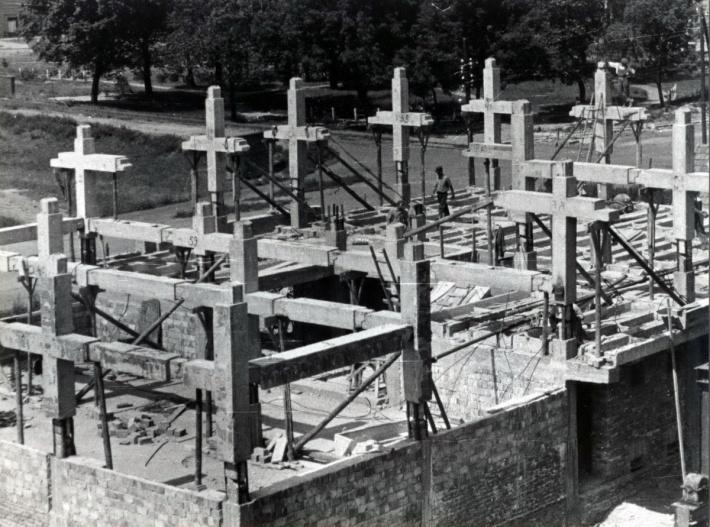 Az épület szerkezetének építése. Jól kivehetőek a kereszt alakú fő tartóelemek. Egymáshoz való csatlakozásuk oszlopközépnél és a gerendák nyomatéki nullpontjánál történt. (fotó: GYŐRITERV-es kiadvány)
