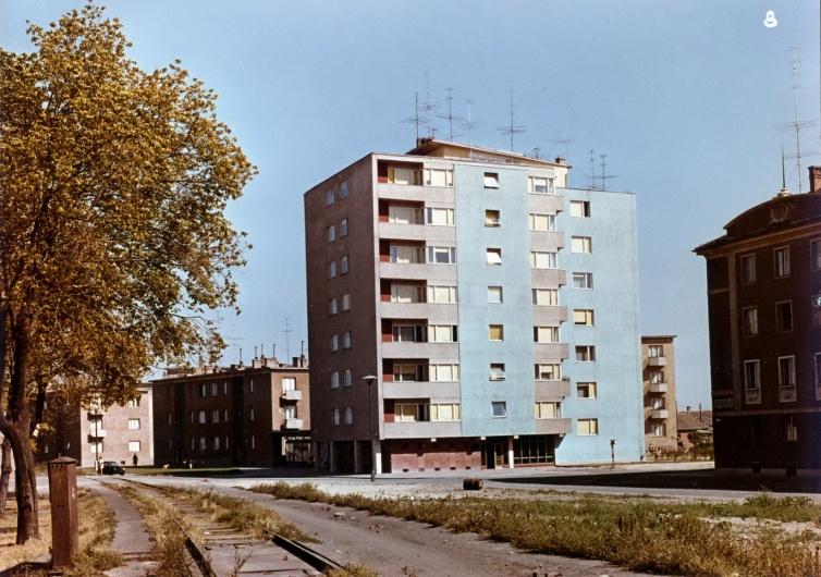 Hétemeletes lakóépület a Mester utca és Tihanyi Árpád út sarkán. Bár szerkezete már előregyártott, még lehetőség volt egyes egyedi elemek kialakítására. Ilyen például a ferdén lefedett lépcsőház felülvilágító. A fotó még az eredeti, kék színezését mutatja a házat. (fotó: archív)