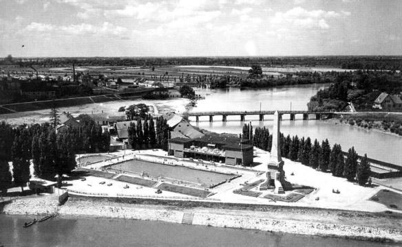 """Az új strand a Mosoni-Duna és a Rába találkozásánál. A kép bal oldalán látható a gyalogoshíd vége a pénztárakkal. Középen a strand két medencéje (versenymedence és gyermekmedence) az öltözőépülettel, valamint a Cziráky emlékművel. Háttérben a """"tízlábú"""" híd és a szabályozatlan Mosoni-Duna. (forrás: Winkler-Kurcsis)"""