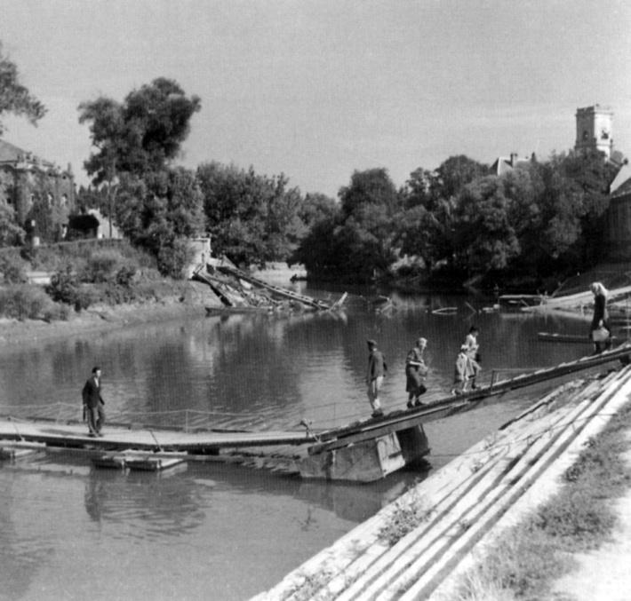 Háttérben a lebombázott híd roncsa, előtérben az ideiglenes gyalogoshíd. (archív)